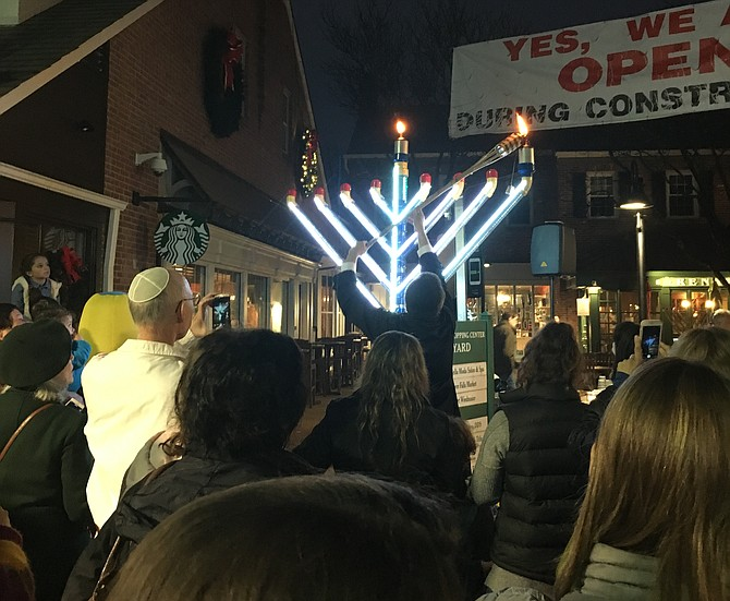 Rabbi Mendel Kaplan lights the candle celebrating the first night of Chanukah Sunday. Chabad of Potomac sponsored the candle lighting which included latkes, donuts, music and entertainment at the Potomac Place Shopping Center.