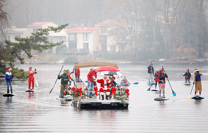 "Santa is escorted by an entourage of his best paddleboard elves as he prepares to dock at Lake Anne Plaza in Reston for the highly anticipated ""Jingle on the Lake"" produced by Lake Anne Merchants."
