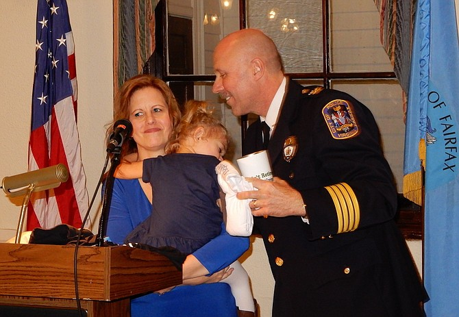 Cathy and Carl Pardiny with sleepy granddaughter Sydney, 2½, during the ceremony.