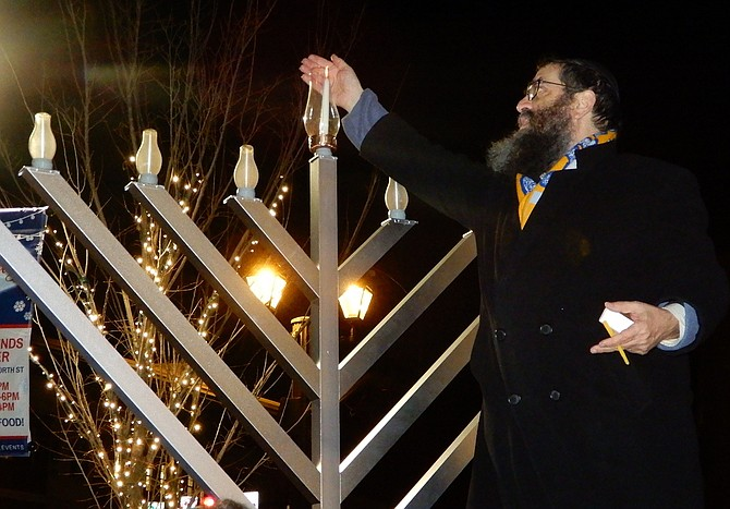 Rabbi Sholom Deitsch lights the Chanukah menorah in Old Town Square.