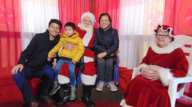 Zhengia and Winston Meng and Xiao Lan Cheng of Vienna visit Santa and Mrs. Claus, a.k.a. Rodney and Janet Smith.