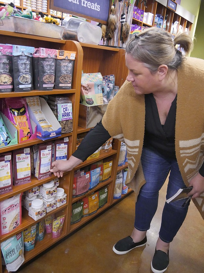 "Regan Chinn, area manager for Kriser's Natural Pet, points out some of the favorite Vital Cat cans. ""Minnow is very popular."""