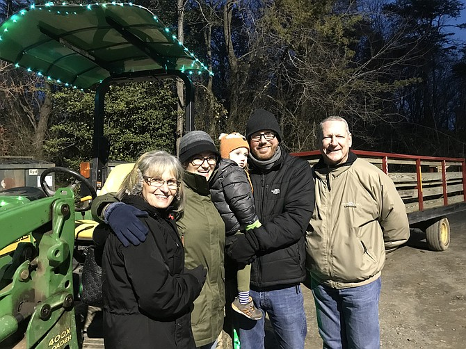As the tractor-driven Starlight Express at Lake Fairfax prepares to load, the Schroeder family of Springfield, April, Harper 2 1/2 and Shane (center) pause to capture the moment with April's parents, Cindy and Chip Paris of Wooster, Ohio (far left and right).