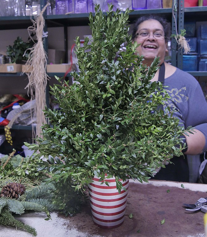 Shakeela Doskas has completed the greenery on her centerpiece and proceeds to the final stages.