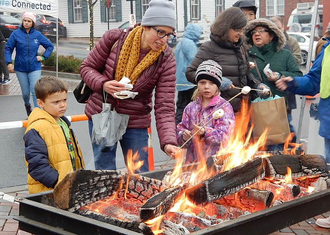 Dee Hammell helps son Isaac, 4, and daughter Josephine, 7, toast marshmallows for s'mores.