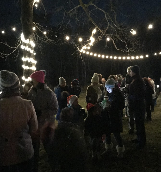 Families line up under the twinkling lights for a personal chat with Santa during the 2nd Annual Santa, Stars, & S'mores held at Runnymede Park in Herndon.