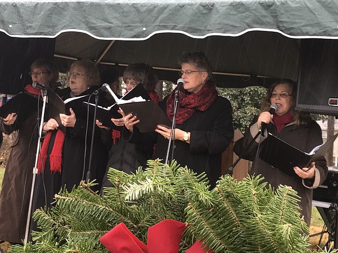 Members of the Bobby Pins, a group within Reston Chorale, (from left) Ellen Torzilli, Jo Marshall, Kate Schindler, Susan Wagoner, Kit Kobran and (not pictured) Al Torzilli sing as participants place wreaths on veterans' gravesites.