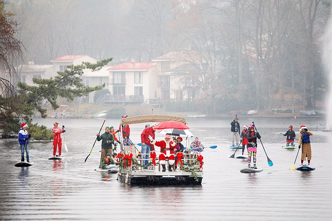 Sharing Holiday Spirit: Santa is escorted by an entourage of his paddleboard elves as he prepares to dock at Lake Anne Plaza in Reston for Jingle on the Lake on Dec. 1, 2018. The pages of the Connection Newspapers have been full of holiday spirit, beginning before Thanksgiving.