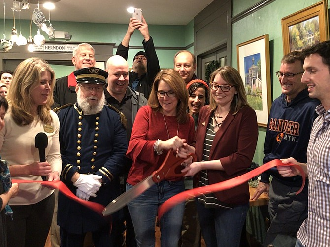 Officially opening historic Herndon's newest business, Elden Street Tea Shop, (center) Mayor Lisa C. Merkel and Rachel Eisenfeld cut the ceremonial ribbon while (far left) Vice Mayor Jennifer Baker, (second row) Town Councilmember Bill McKenna, Del. Jennifer Boysko (D-86) and District 33 Senate candidate, (third row left) Mike O-Reilly, former mayor of Herndon and current member of the Dulles Chamber of Commerce and John Boylan, President and CEO of the Dulles Chamber of Commerce cheer them on.
