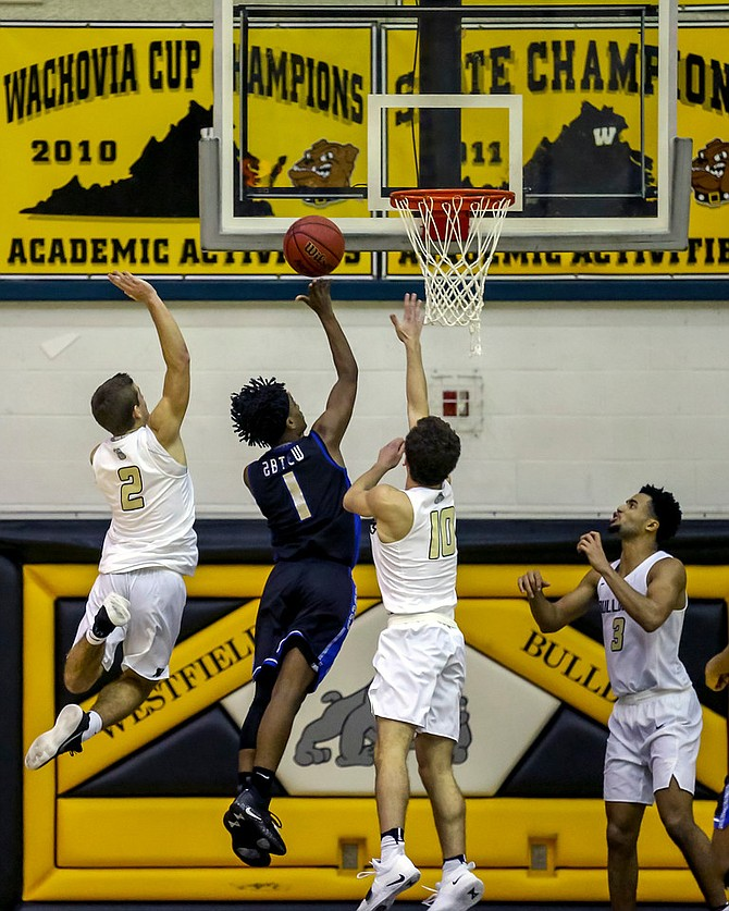 Josh Abtew #1, who led Fairfax with 18 points, tries to avoid Westfield's Taylor Morin #2 and Kamran Zahory #10.