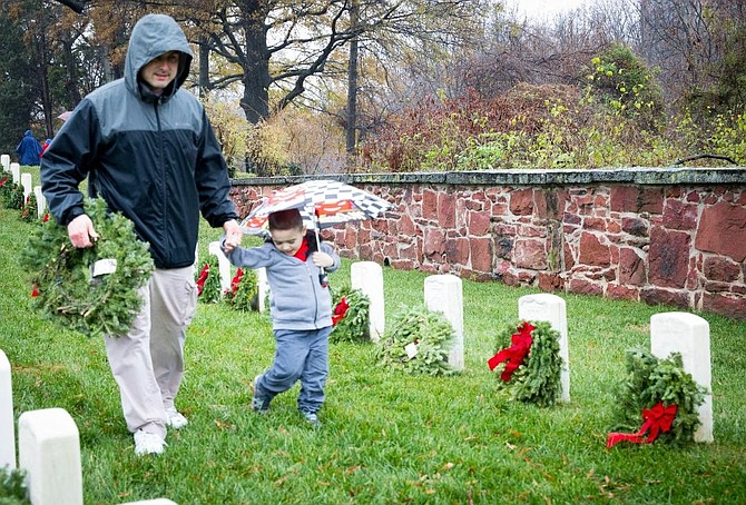 A father and son carry a wreath to place at the grave of a veteran Dec. 15 as part of Wreaths Across America at Alexandria National Cemetery.