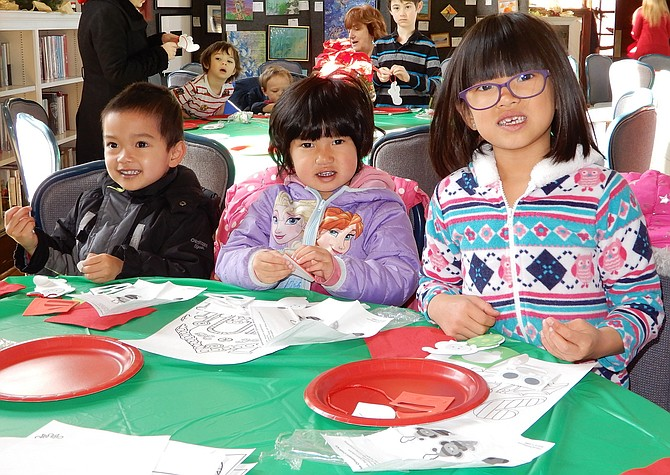 From left, Clinton Tran, 3, Maygan Cao, 3½, and April Cao, 6½, make Christmas ornaments together.