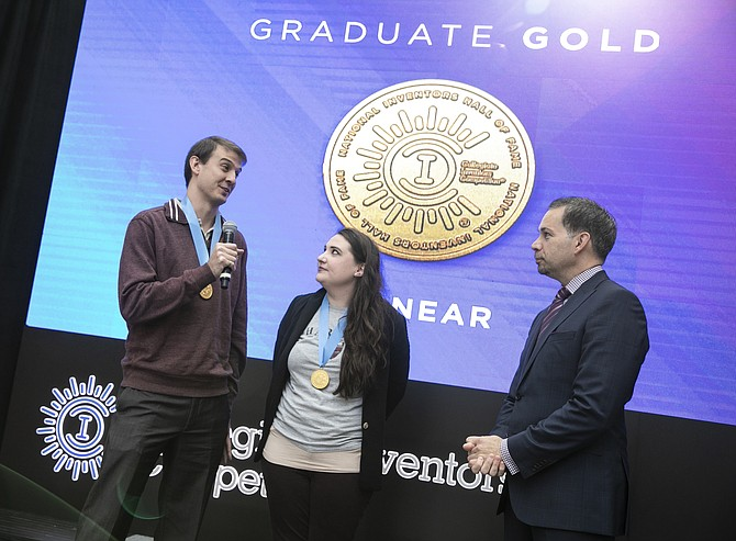 PionEar team members Michael Kreder and Nicole Black speak on stage with Anthony Scardino, USPTO chief financial  officer, after winning the Graduate Division gold medal Nov. 16 at the 2018 Collegiate Inventors Competition.