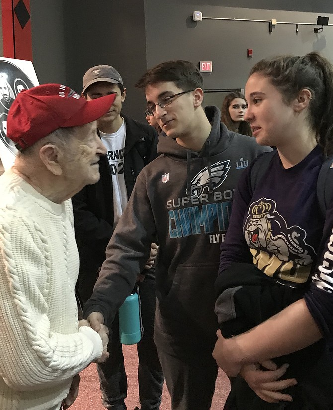 Mathew Steil, 17, and Zoey Birman, 16, Herndon High School Band members, thank Rubin Sztajer, Holocaust survivor for coming to speak to The Pride of Herndon before the students' upcoming spring trip to Normandy for the 75th Anniversary of D-Day.