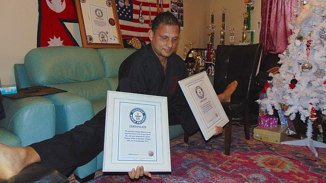 Three-time Guinness World Record holder Ujjwal Sharma Thakuri of Springfield does a Van Dam-style split in his living room.