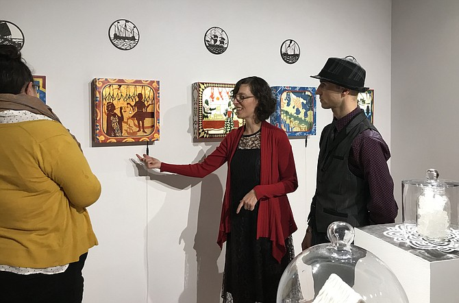 "Artist Melanie Kehoss explains her work to patron Jennifer Biehl as Kaveh Jorab looks on during the opening of the exhibit, ""Mary B. Howard Invitational: Stretch,"" now through Feb. 9, 2019."