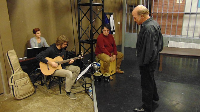 """John Hollinger, who plays Cervantes in """"Man of La Mancha,"""" rehearses a song with the band."""