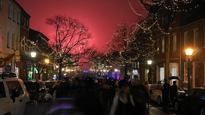 The First Night Alexandria fireworks turned the low cloud cover above the waterfront a fiery shade of red as revelers rang in the New Year at the foot of King Street.