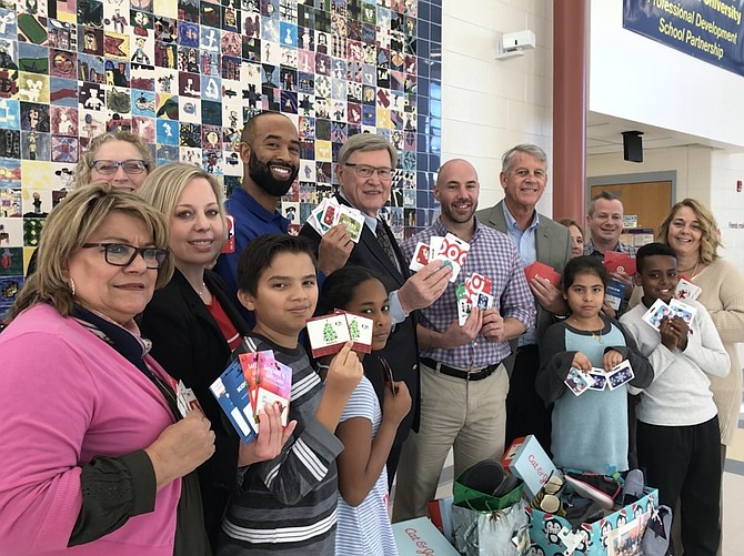 From left, Maria Michlik, parent liaison; Asman Khanal, 10; Aseel Hamza, 9; Lesley Avila Lopez, 9; Abem Teshale, 9; Jenny Phipps, legislative aide for Supervisor Foust; Katie Aldridge and Steven Wilson, Assistant Principals, Hutchison E. S.; Supervisor John W. Foust (D-Dranesville); Ray Lonnett, Principal of Hutchison E. S.; Mike O'Reilly, Chairman of the Board Arts Herndon; Anna Schoenfeld, Director Exhibits, Arts Herndon; Jason DiMambro, Director Outreach Arts Herndon; and  Renee Gorman, School Counselor Hutchison E.S.; display donations from Supervisor John W. Foust's annual holiday shoe drive to benefit students in need at Hutchison E.S. in Herndon.