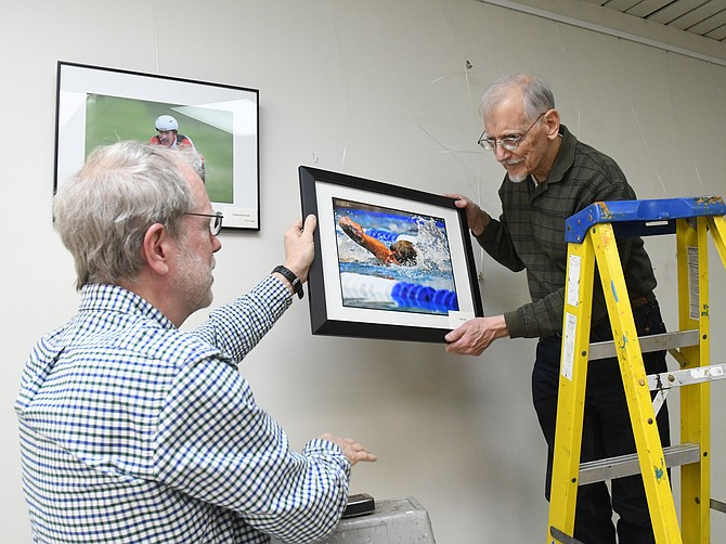 RSVP Northern Virginia volunteer photographers George Bradshaw, right, and John Olsen prepare a special exhibit featuring photos from the 2018 Northern Virginia Senior Olympics, Dec. 13, 2018,  at the Oak Marr RECenter in Oakton.