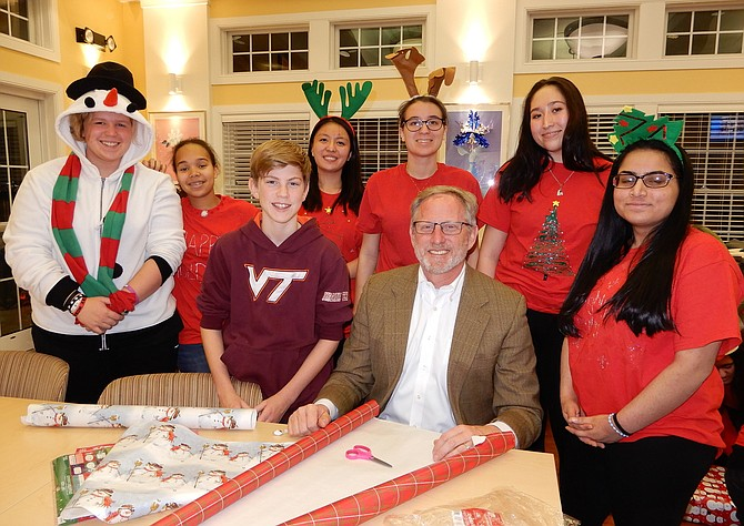 Wrapping presents for the children are Chantilly High Principal Scott Poole and son Jake, 12, plus Chantilly students (from left) Danielle Hawkett, Isis Holmes, Ariel Yang, Brianna Gordon, Isabelle Sheard and Javeria Zulfqar.