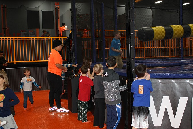 Children watched as others jumped and ducked from the rotating bar.