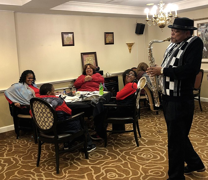 Lolita Robinson and her family are photographed with saxophonist Keith Kool-K Wilson entertaining the group.