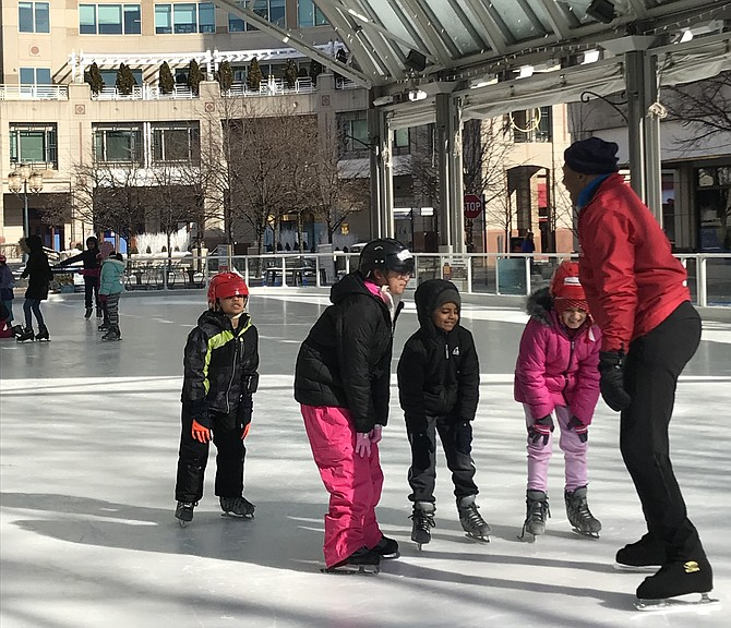 During one of the Learn to Skate Beginner Lessons held Saturday morning, Feb. 2 at the Reston Town Center Ice Skating Pavilion, students practice bending their knees a bit and placing their hands on them while keeping heads up and eyes forward to maintain their center of gravity, gaining control and balance.