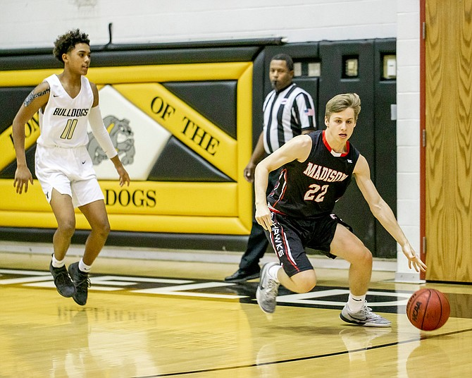 Madison's TJ Ulrich #22 dribbles the ball up the court trying to avoid the full court pressure of Westfield.