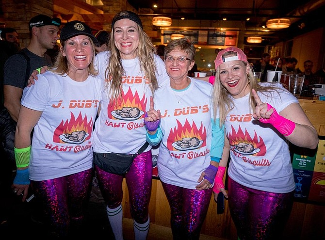 Del Ray Realtor Jen Walker, second from right, and her teammates pose for a photo after competing in the 500-meter indoor cycling sprints Feb. 4 at Pork Barrel BBQ. The event was part of a fundraiser to support VeloCity Bicycle Cooperative co-founder Christian Myers, who is battling cancer.