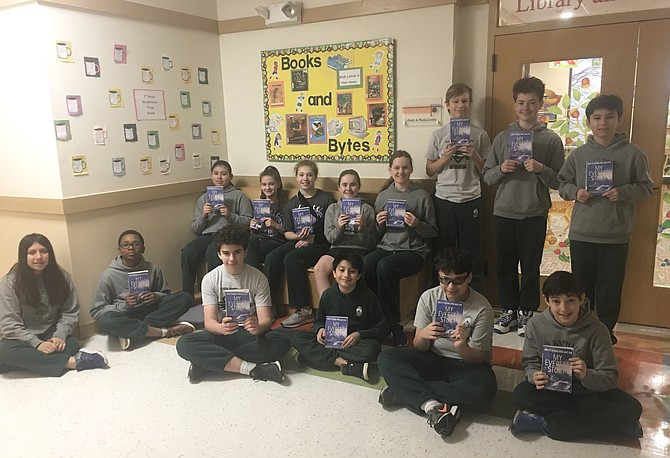 "The 7th grade language arts class at St. Raphael School hold their copies of ""Within Reach: My Everest Story"" by Mark Pfetzer and Jack Galvin."