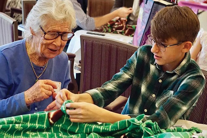 Vinson Hall resident Valerie Vesser and Potomac School ninth grader Ethan Norton enjoy chatting as they work together to create a knot-edged blanket.