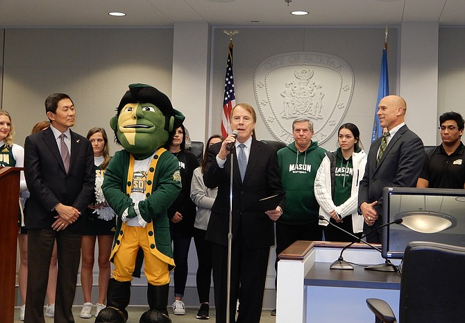 During a City Council meeting, Fairfax Mayor David Meyer (center) declares February as GMU Patriots Month in the City, while the university mascot and representatives look on.