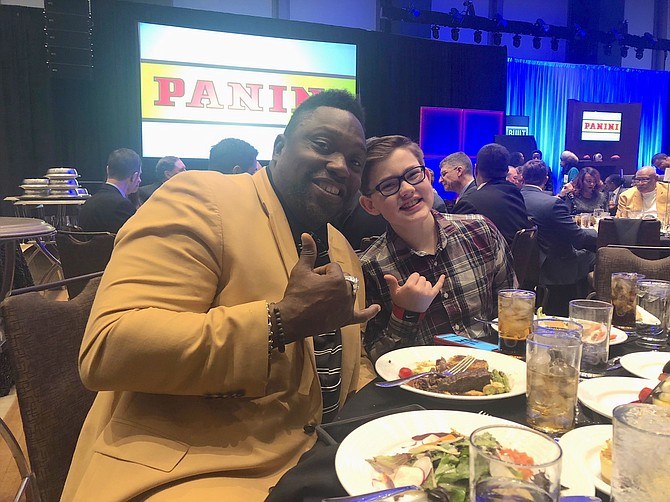 Panini America Super Bowl Kid Reporter Corbin Boehm enjoying a fun moment with one of his favorite players, former Tampa Bay Buccaneer and NFL Hall of Famer, Warren Sapp.