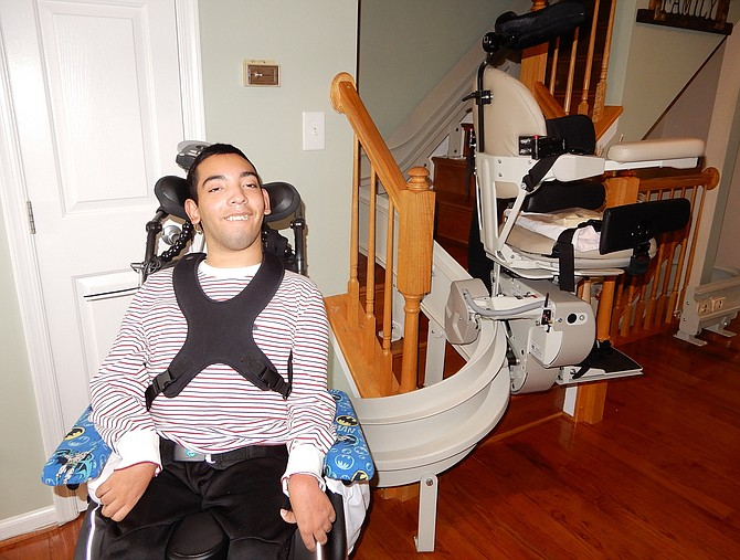 Juwaan Espinal poses beside the chair lift that takes him upstairs to his bedroom via a special rail.