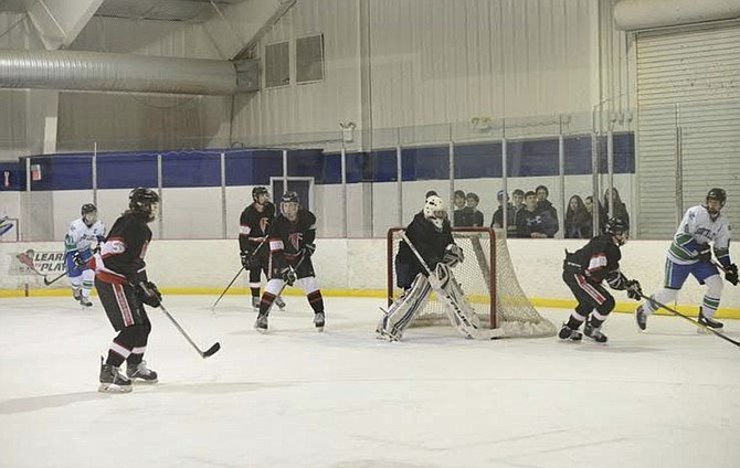 Warhawk Ice Hockey players protect their goalie during a recent game against South Lakes. Madison back-up goalie and Team Captain Luke Pohlman turned away 26 shots. The Warhawks lost 1-2 but went on to secure a spot in the Northern Virginia Scholastic Hockey League (NVSHL) playoffs.