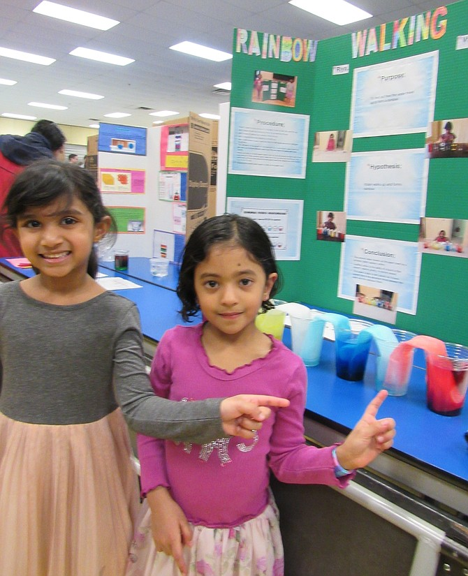 (From left) Riya Nanduri, 5 and Vritika Chilukamarri, 5 of Herndon explain their procedures and the purpose, hypothesis and conclusion for their  Rainbow Walking Water Project.