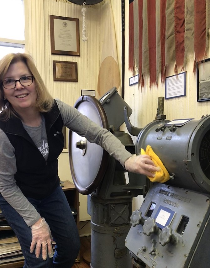 Nancy Saunders, Board President of the Herndon Historical Society, gives artifacts in the Herndon Depot Museum a gentle cleaning.