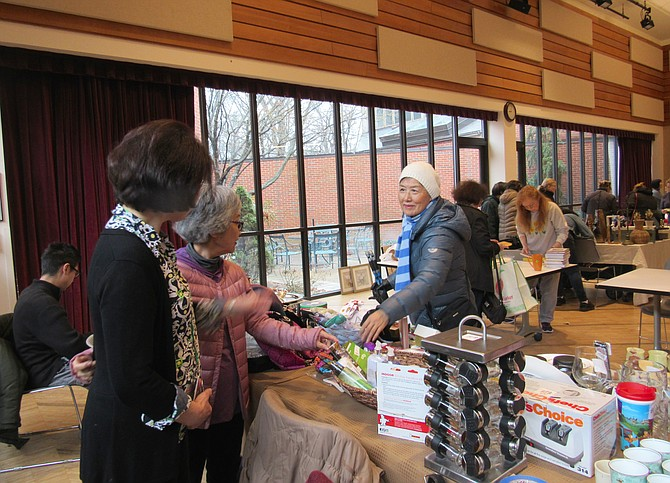 From left, vendors Sumi Gallas of Reston and Yumi Shintani of Herndon help a customer with her selection at Spring Flea Market RCC Hunters Woods.
