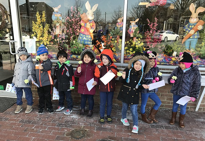 Children from HCC Preschool hold carnations given to them by staff at Herndon Florist after the employees explained their service roles as community helpers in the Town of Herndon.