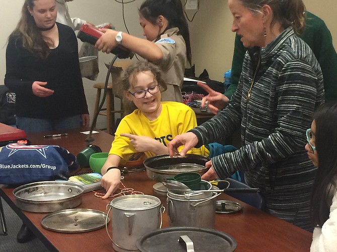 Assistant Scoutmaster Karen Downs helps Scouts sort through the troop's cooking supplies.