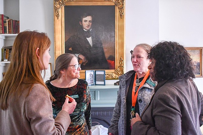 Leslie Herman, Director of Parks and Recreation, Leigh Kitcher, VP of Historic Vienna,  and Gloria Runyon, member of Historic Vienna, listen to Anne Stunz, President of Historic Vienna (second from right), talk about the exhibits.