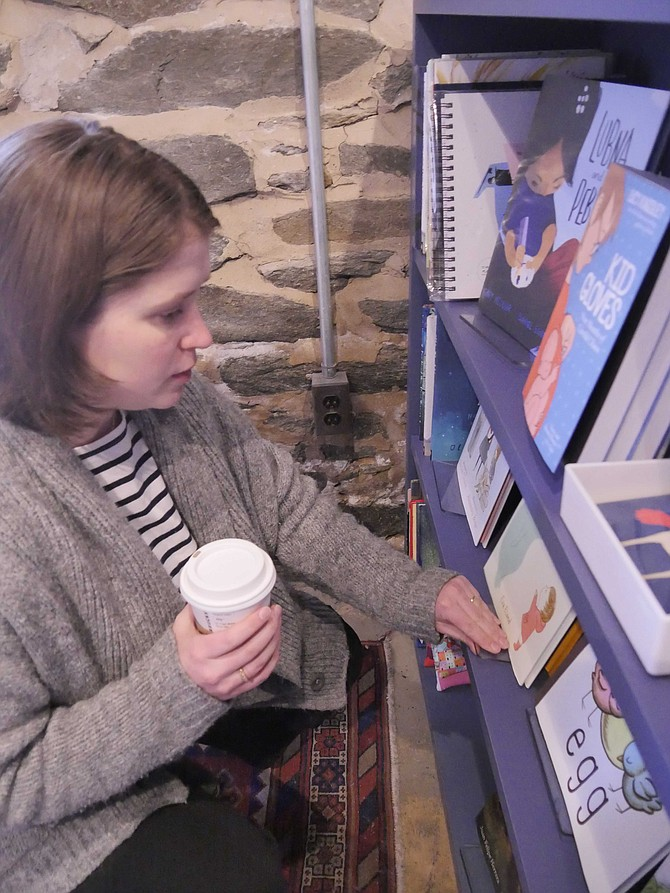 Ally Kirkpatrick looks through her selection of children's books at Old Town Books. She likes to give children something they haven't see before — in addition to the classics.