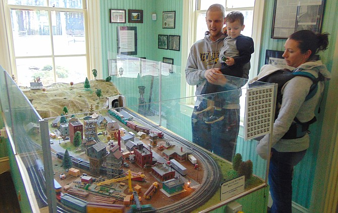 Greg and Christina Kranz of Springfield with their children Quincy and Monty admire the train set.