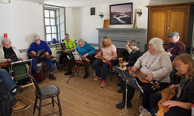 The Mountain Dulcimers — (from left) Linda Hubbard, Lewis Cabe, Noel Schroeder, Kathy Wilson, Marcia Price, Karen Buglass, Jim Weed, Maddie MacNeil, and Carol Whitmer — perform music from the 19th century at Great Falls Tavern Visitor Center, on Saturday, March 16.