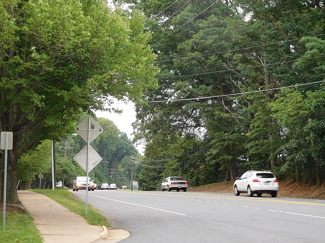 During spring, green trees form a scenic background for vehicles driving on Old Lee Highway.
