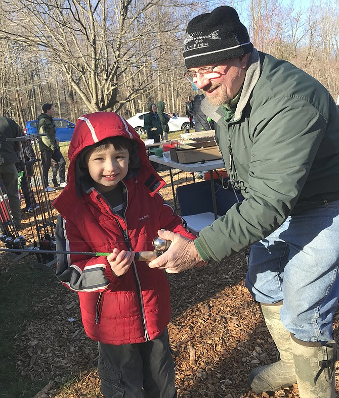 Bradley Wang, 6, of Reston, shivers in the cold, but is prepared to catch his first Rainbow Trout during Reston Association's annual Kids' Trout Fishing Day 2019.
