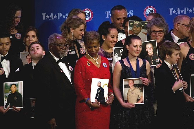Family members of fallen military veterans hold photos of loved ones at the TAPS Honor Guard Gala March 6 to mark 25 years of the organization's service to military family survivors.