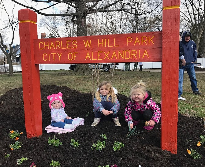 Eleanor, Laila and Audrey Hill sit among the newly planted flowers at the Charles W. Hill Park in Del Ray. The park is named for their late grandfather, Corporal Charles Hill, the last Alexandria police officer to be killed in the line of duty.