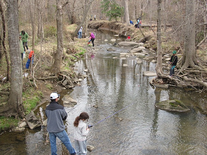 Families enjoy a warm spring morning along the stream banks of Sugarland Run in Herndon during the 2019 Kids Trout Fishing Derby.
